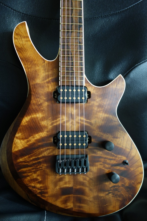 This is a Figured Imbuya Top with Contoured Armrest. It is a solidbody guitar with a Black Limba back and a Roasted Maple neck. It will be equipped with jescar EVO gold frets, hipshot hardware , Dimarzio Dominion Bridge and Neck pickups. Its 26″ Scale length with 6 strings tuned to E Standard half step down by Default. This model was finished with Odies Oil and Wax.